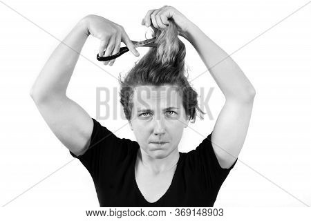 The Girl Is Holding A Pair Of Scissors And Trying To Cut Her Own Hair. Haircut At Home Or On Your Ow