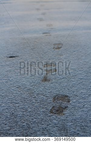 Shoeprints On Icy Ground. Human Feet Traces, Shoes Imprints On White Snowy Road. Fresh Snow Fallen O