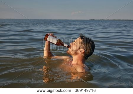 Young man having a good time drinking beer and refreshing in the water at the beach