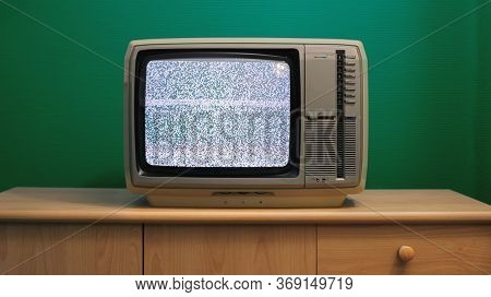 No signal just noise on old analogue TV set in front of green wall