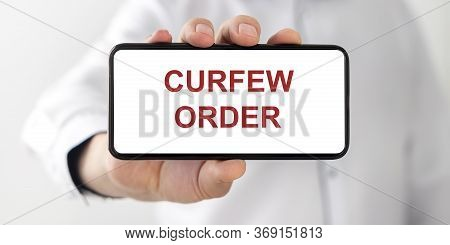 Curfew Order Text Words Inscription On White Phone Screen In Male Hand On White Background