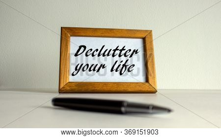 Wooden Picture Frame With Inscription 'declutter Your Life' On Beautiful White Fon. Pen On The Table