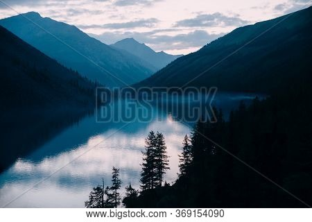 Silhouettes Of Larches On Background Of Highland Lake And Mountains Silhouettes. Fog Along Shore. Re