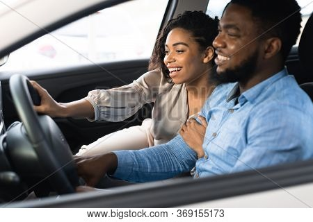 Cheerful Black Couple Testing Car During Test-drive Buying Auto In Dealership Center. Selective Focu