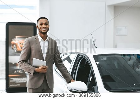 Automobile Seller Man Opening Car Door Selling Cars Smiling To Camera Standing In Auto Dealership Sh
