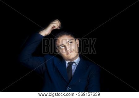 Portrait Shot Of A Confused Thinking Man In Blue Suit With His Hand Over His Head Isolated On Black
