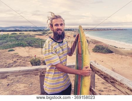 Attractive Blonde Australian Hipster Surfer With Dreadlocks And Beard Looking At The Sea Holding Coo