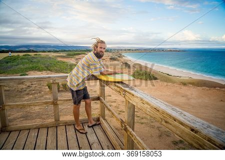 Portrait Of Hipster Surfer With Dreadlocks And Beard Looking At The Ocean With Vintage Surfboard .