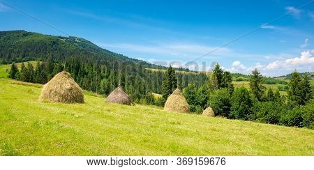Summer Landscape Of Rural Valley. Stack Of Hay On A Green Meadow In The Mountains In The Morning Und