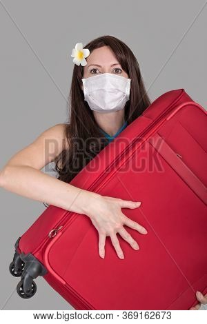 Frightened Tourist Woman In A Medical Mask Presses With Red Suitcase, Flights Canceled