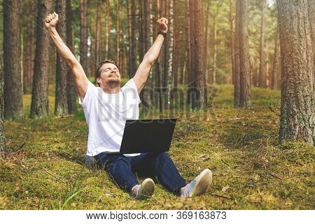 Remote Job - Man With Laptop Enjoying Working Outdoors. Hands Raised