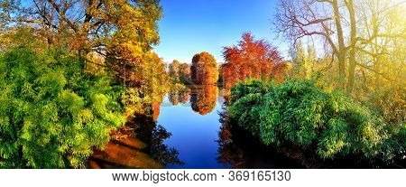 Colorful Flora Around A Blue Lake In A Park In Autumn, With Red, Green And Yellow Foliage, Nice Weat
