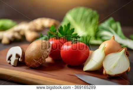 Preparing Vegetables On A Wooden Cutting Board To Cook. A Closeup With Shallow Focus Showing Colorfu