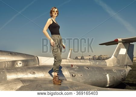 Beautiful girl pilot stands on the wing of a fighter airplane at the airfield.