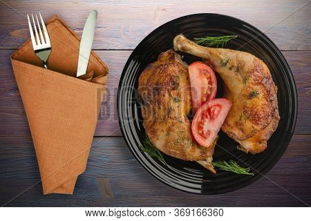 Chicken Thigh With Vegetables On Purple Wooden Background. Chicken Leg On Blac Plate With Fork And K
