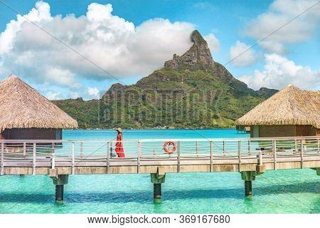 Luxury paradise honeymoon destination travel Bora Bora island overwater bungalows hotel vacation in Tahiti, French Polynesia. Woman walking on idyllic resort beach.