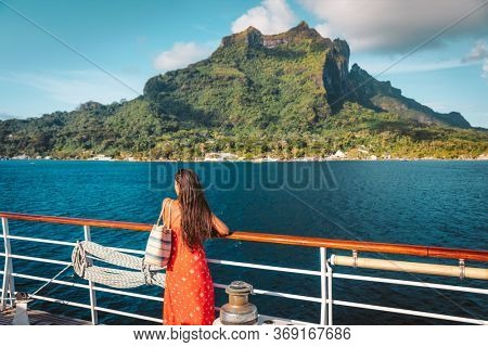Cruise ship travel vacation luxury tourist woman looking at Bora Bora island view from deck of sailing boat, Tahiti French Polynesia destination lifestyle. Summer getaway idyllic paradise life.