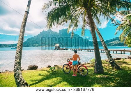 Tahiti travel biking tourist on electric bicycle rental in Bora Bora island , French Polynesia eco-tourism summer vacation adventure fun cyclist girl relaxing at landscape on E-bike biking.