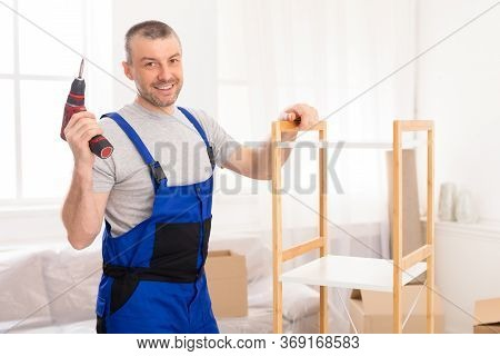 Furniture Assembler Man Posing With Electric Drill Assembling Cabinet Working Indoor, Smiling To Cam