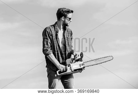 Feeling Confident. Risky Temper. Powerful Chainsaw. Sharp Blade. Handsome Man With Chainsaw Blue Sky