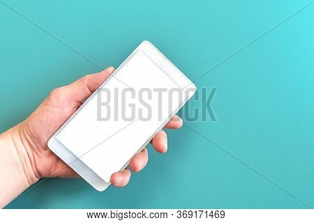 Hand Holding Phone With White Screen On Turquoise Background. Smartphone Device In Hand On Blue Back