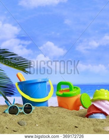 Summer Vacations. Plastic Toys For Kids Activities On A Sandy Beach. Blur Sea Background