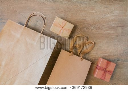 Craft Paper Bags And Cardboard Blank Boxes Presented On Rustic Wooden Background. Unlabeled Cardboar