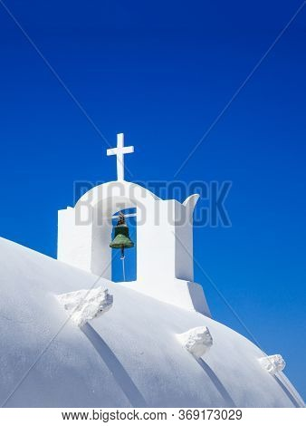 Summer Vacation At Santorini Island, Greece. White Orthodox Greek Church With Cross And Bell