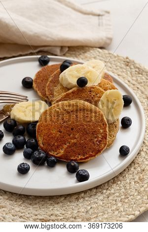 Vertical Image Of Banana Oatmeal Pancakes Served With The Slices Of Banana And Blueberries On The Ro