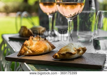 Traditional Argentine Empanadas With Beef Stuffing And Glasses Of Rose Wine.