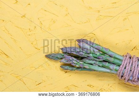 Green And White Fresh Asparagus On A Yellow Background