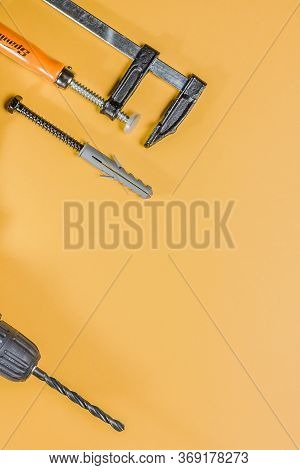 Clamp, Self-tapping Screw With Dowel And Drill Chuck With Black Drill On An Orange Background. Top V