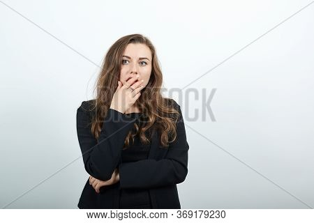 Young Attractive Woman Brunette In In Black T-shirt And Sweater On White Background, Terrified Woman