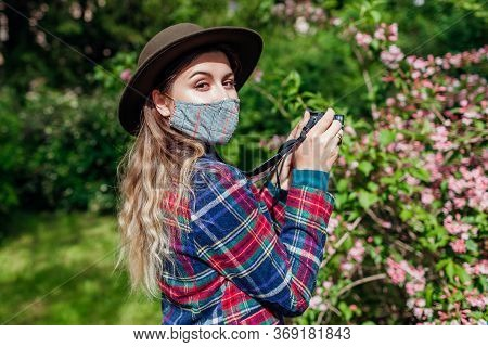 Woman Photographer Taking Photos Using Camera In Summer Garden Wearing Coronavirus Protective Mask.