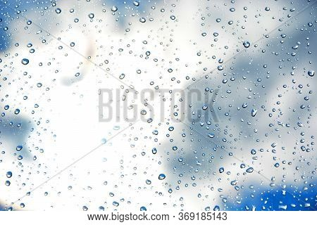 Raindrops On The Transparent Window Pane, Against A Blurry Blue Sky With White Clouds. Background Of