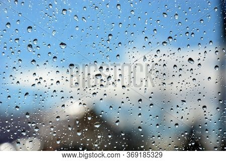 Raindrops On The Transparent Window Pane. Background Of Raindrops On A Wet, Gray And Opaque Glass Te