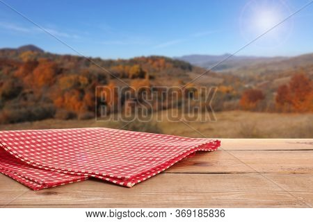 Picnic Wooden Table With Checkered Red Napkin And Picturesque Landscape On Background