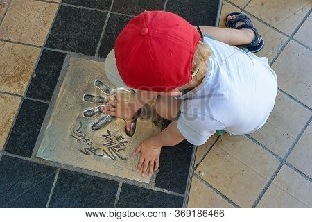 Cannes, France - June 12, 2019 : A Child Testing His Hand In The Handprint Of The Famous American Ac