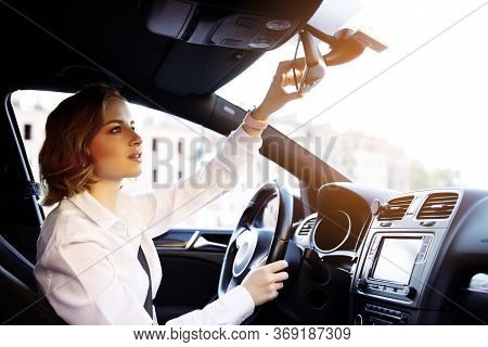 Business Woman In White Shirt, New Driver Sitting In Car, Riding On Road, Adjustment Of Mirror. Hold