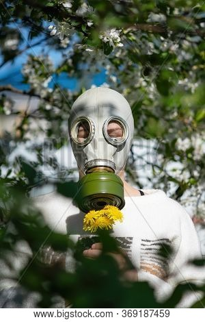 A Woman In A Gas Mask Stands In A Flowery Garden, And Smells The Yellow Flowers . The Concept Of Sea