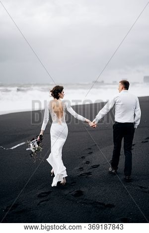 A Wedding Couple Is Walking Along The Black Beach Of Vic. Sandy Beach With Black Sand On The Shores