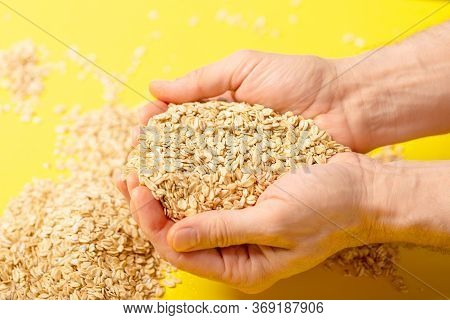 Oatmeal Flakes For Breakfast Holding In Hands On Yellow Background