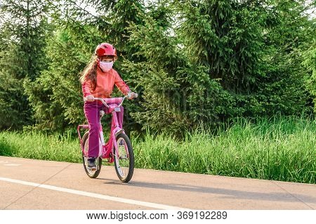 Little Girl In A Protective Mask Rides A Bicycle In A City Park. Copy Space.
