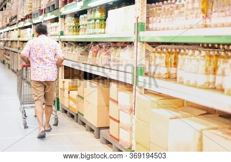 The Back View Man Pushing Shopping Trolley Prepare  Foods And Drink For Stockpiling In The Warehouse