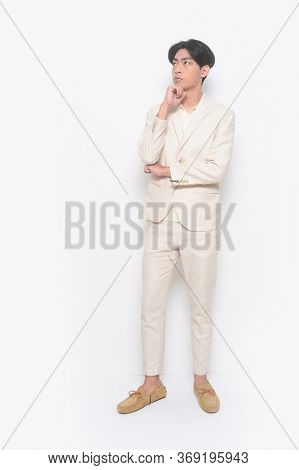 full length Portrait of handsome man wearing white suit with white shirt with casual and brown casual shoes with Put hands prop up on chins.