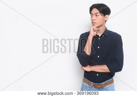 Portrait of handsome man wearing blue shirt with blue jeans put hands prop up on chins.