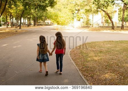 Sisters, Outdoor Photo From Two Little Girls. Two Little Girls Walk In The Park By The Hand. Sisters