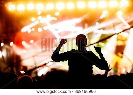 Silhouette Of A Girl With Raised Hands At A Mass Event. Party In A Nightclub