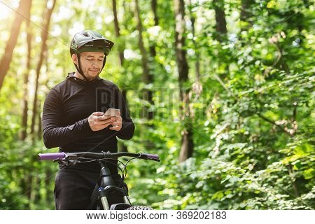 Young Man Rider Standing In Forest, Holding Mobile Phone, Using Online Application For Searching Gps