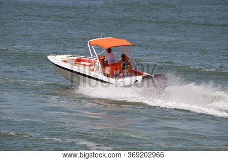 Sporty White Runabout Motor Boat With Orange Trim Powered By Two Outboard Engines.